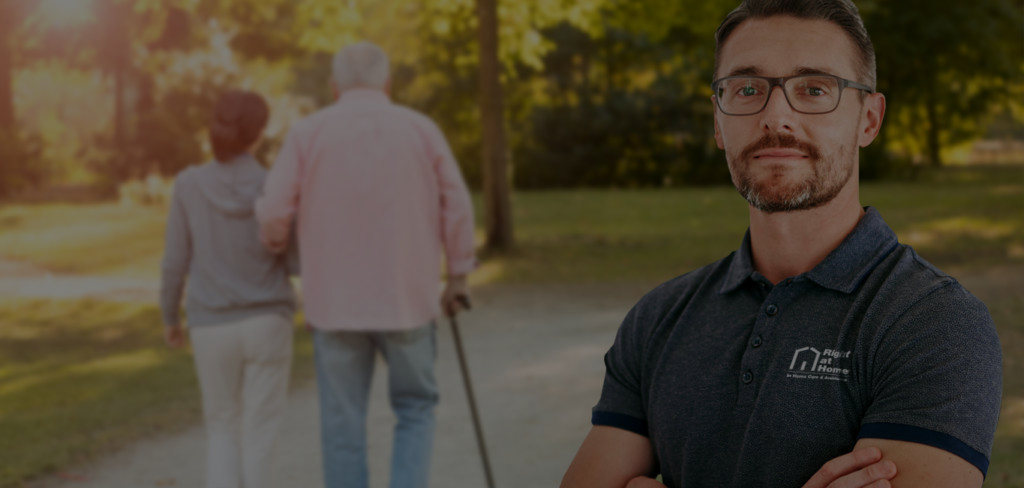 A Right at Home Male Franchisee facing the camera with an elderly couple going for a stroll in a park, walking away from the camera