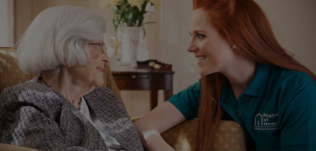 A female Right at Home Caregiver talking with an elderly woman in her chair